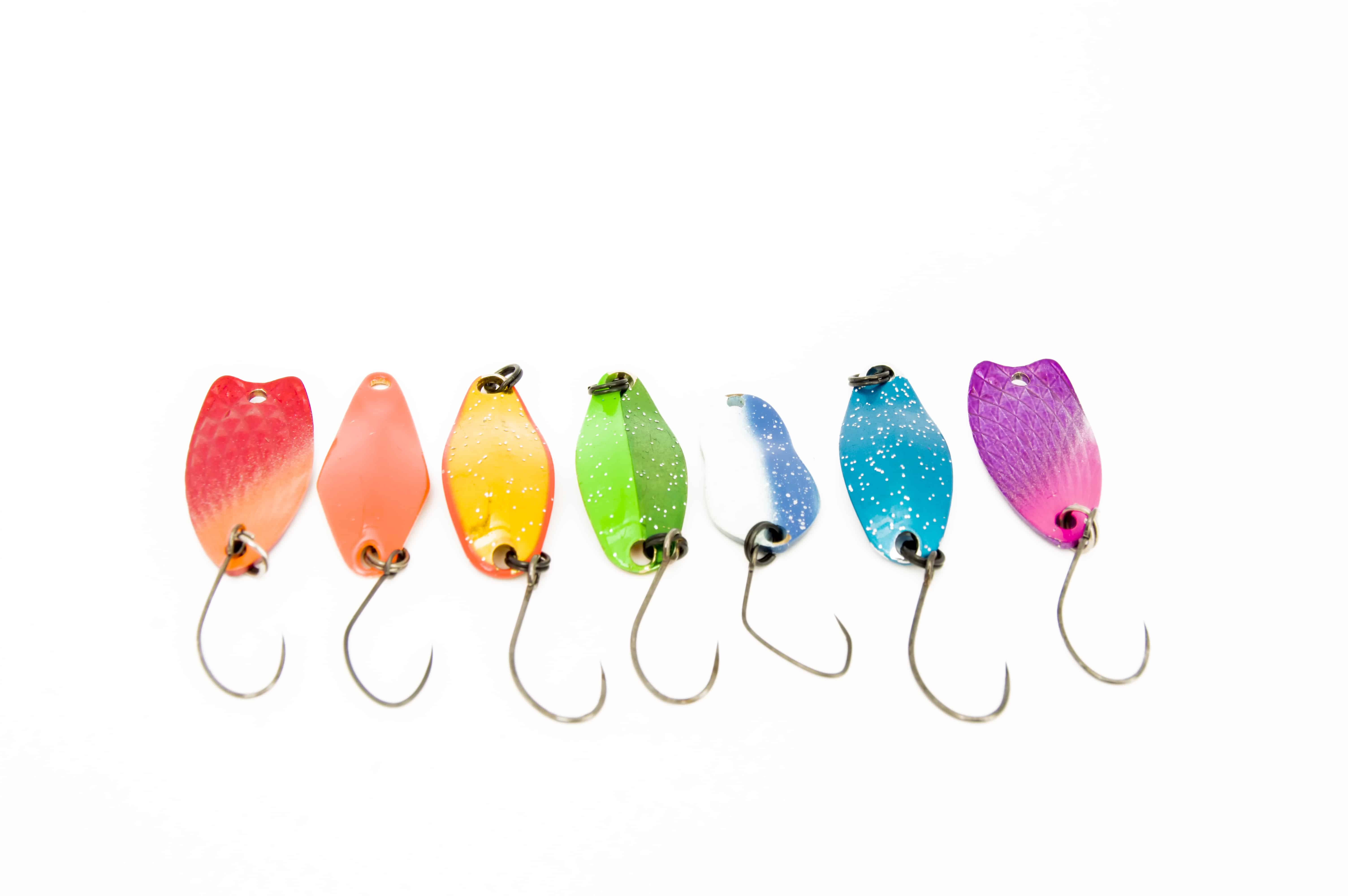Rainbow with ultralite spoons for trout fishing (area fishing) and other fish. Colored hard lures are arranged in a row on a uniform white background top view